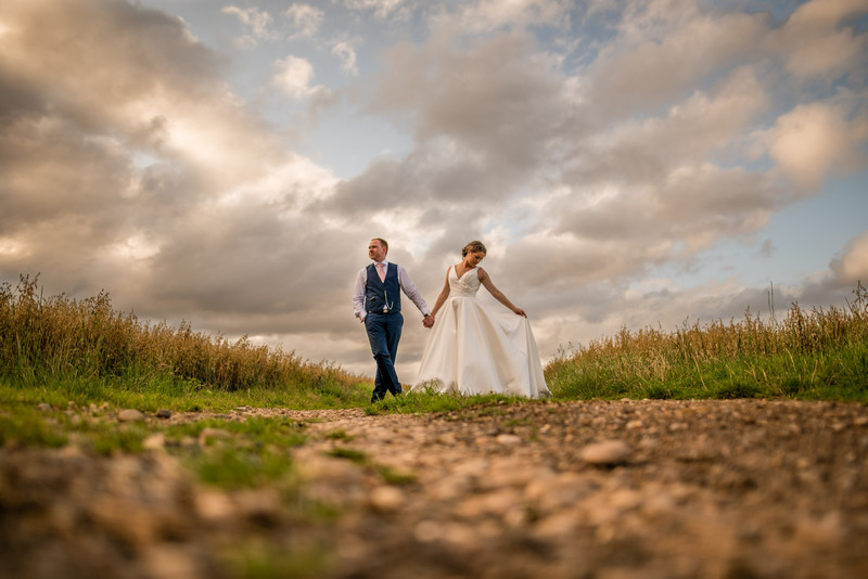 Bride and groom holding hands on path in countryside - Picture by Damian Burcher