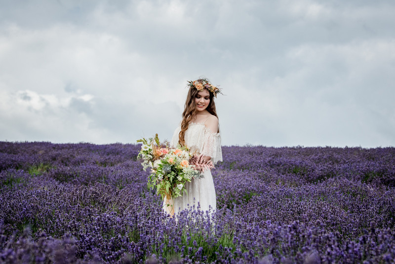 Bride holding bouquet in field of lavender