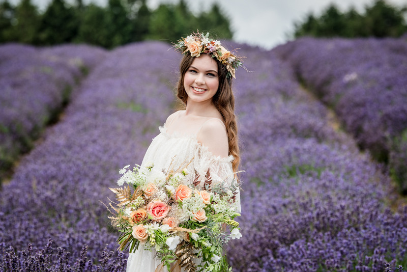 Smiling bride wearing flower crown in field of lavender