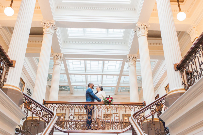 Bride and groom at top of stairs at wedding venue