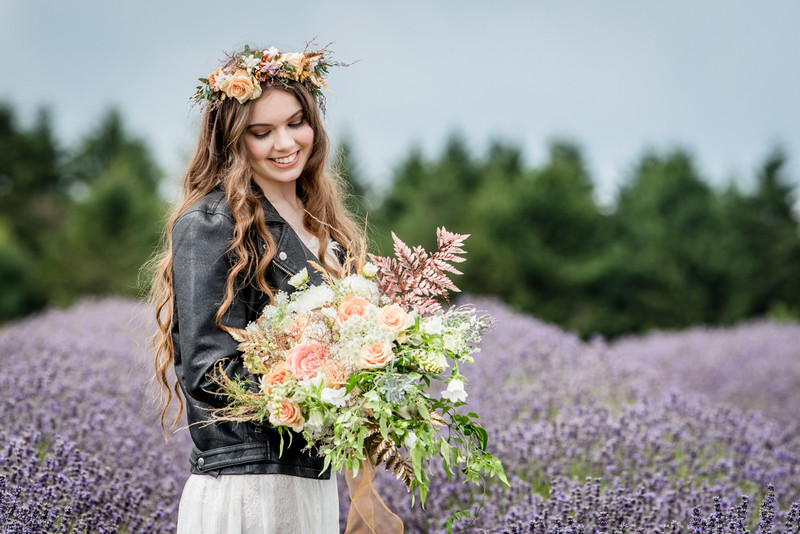 Bride wearing leather jacket standing in Cotswold Lavender Field