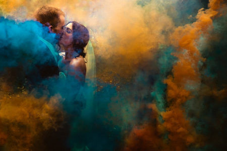 Bride and groom kissing surrounded by orange and blue smoke - Picture by MSW Photos