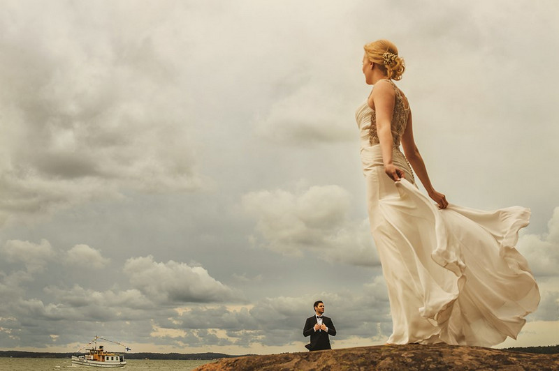 Bride standing looking out to sea with groom in background - Picture by Aleks Kus