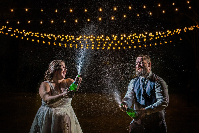 Bride and groom spraying champagne in the dark under fairy lights - Picture by Chad Winstead Photography