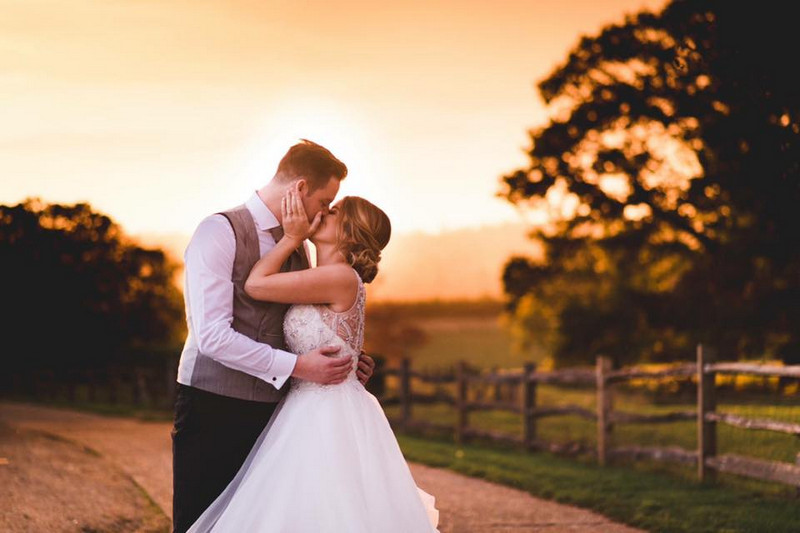 Bride and groom kissing in countryside as sun goes down - Picture by Sophie Oldhamstead Photography