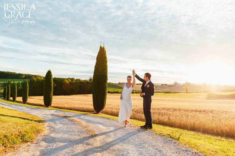 Bride and groom on country road in hazy sunshine - Picture by Jessica Grace Photography