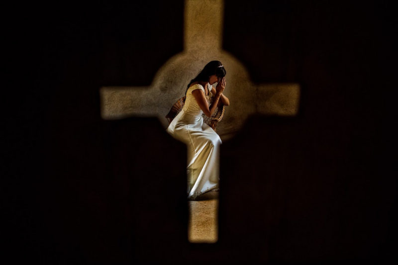 Picture taken through cross of bride praying - Picture by Casian Podarelu Photography
