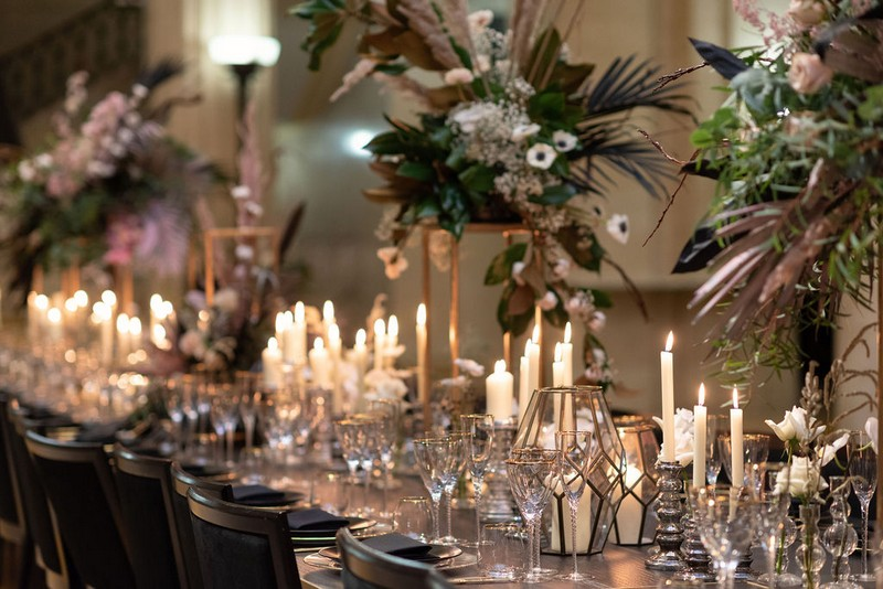 Wedding table styled with candles and large floral displays
