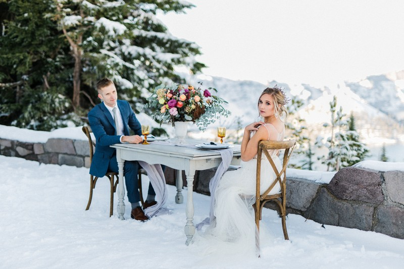 Bride and groom sitting at table outside in the snow
