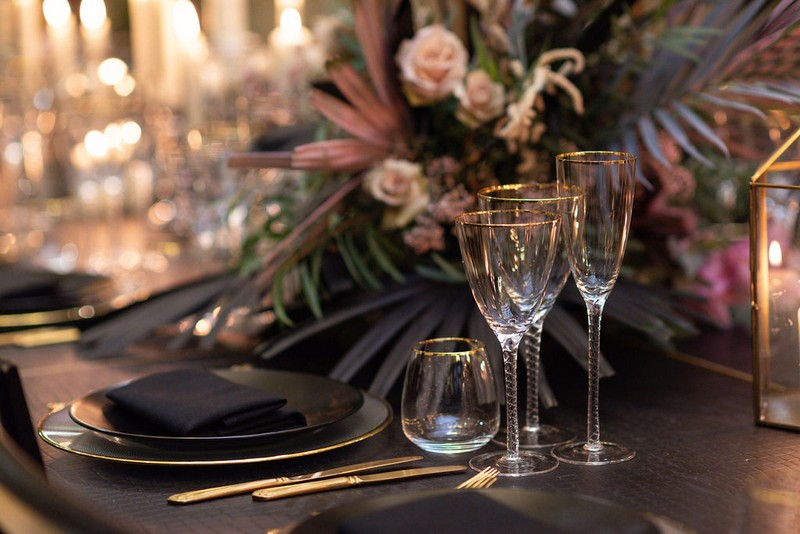 Glasses and large floral display on wedding table