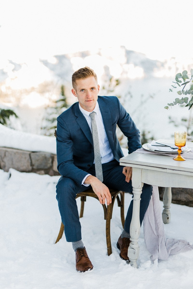 Groom sitting at table in the snow