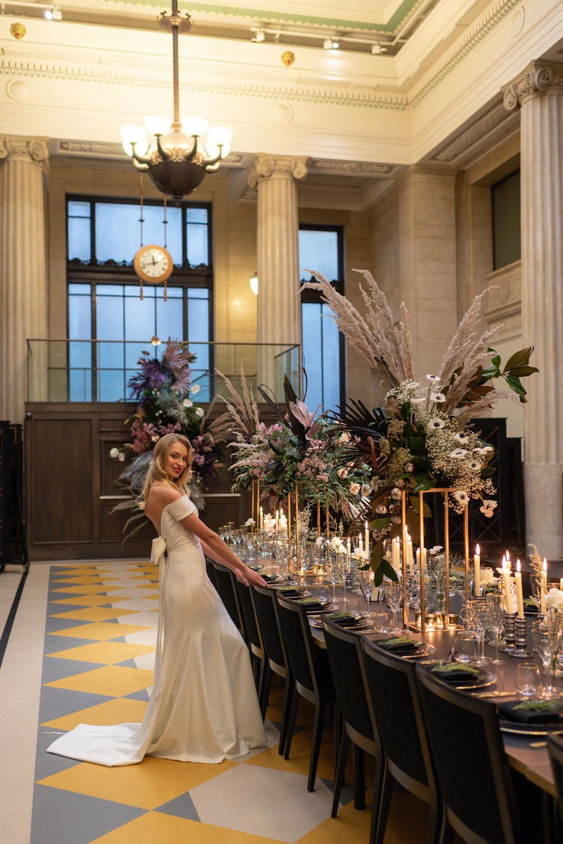 Bride standing next to long wedding table in Banking Hall, London
