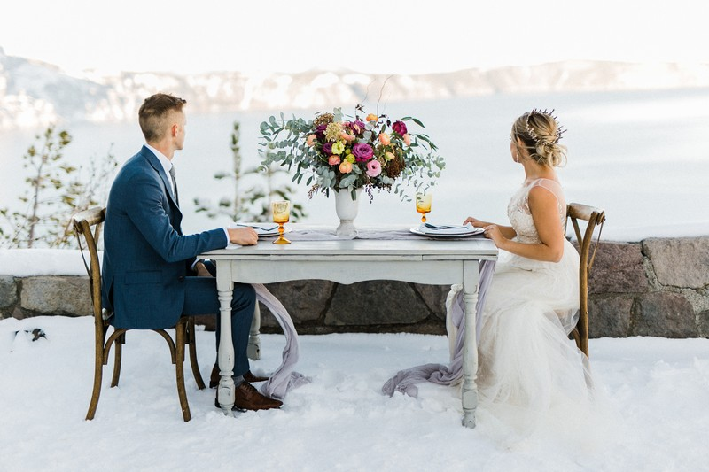 Bride and groom sitting at table looking at view of Crater Lake