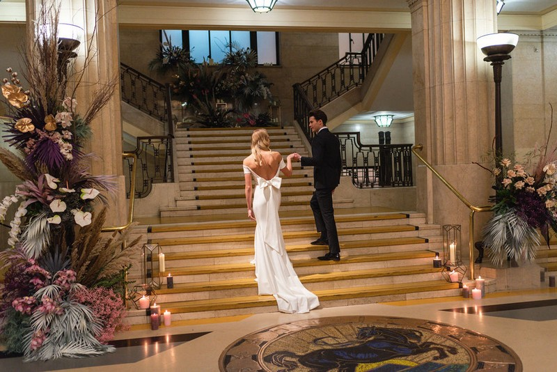 Bride and groom walking up stairs in Banking Hall in London
