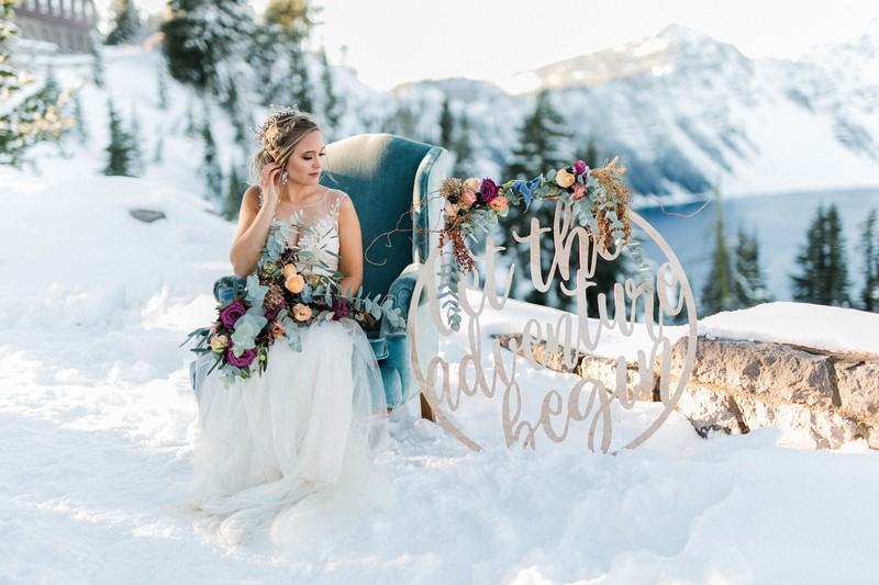 Bride sitting on blue armchair in snow