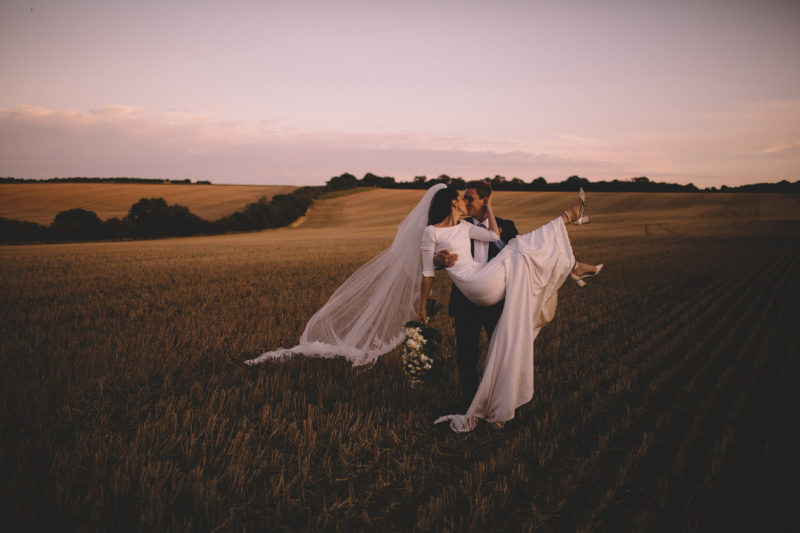 Groom lidting bride up to kiss her in field - Picture by Carrie Lavers Photography