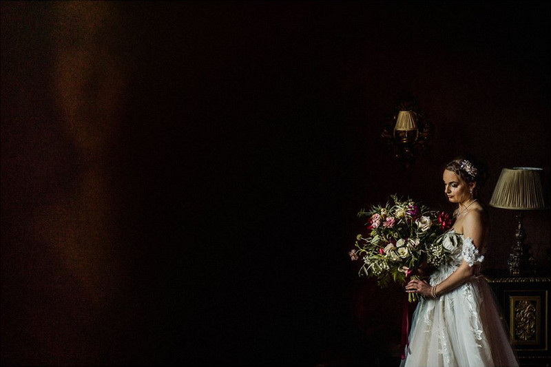 Bride standing holding bouquet in dark room - Picture by Matt Parry Photography
