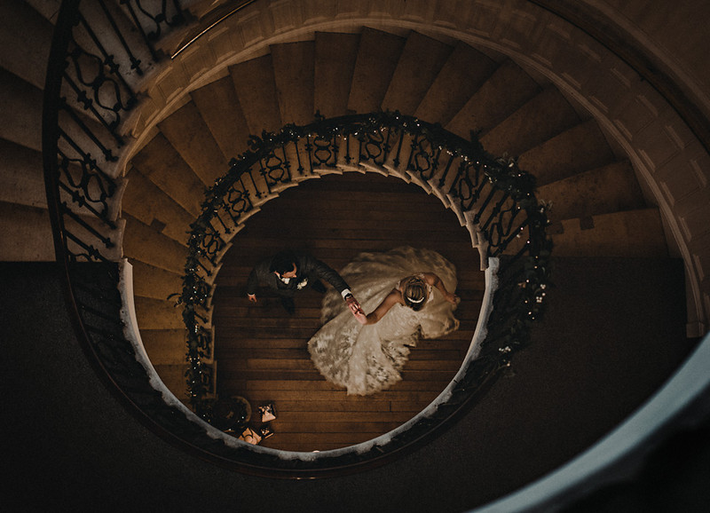 Bride and groom at bottom of spiral staircase - Picture by Oobaloos Photography