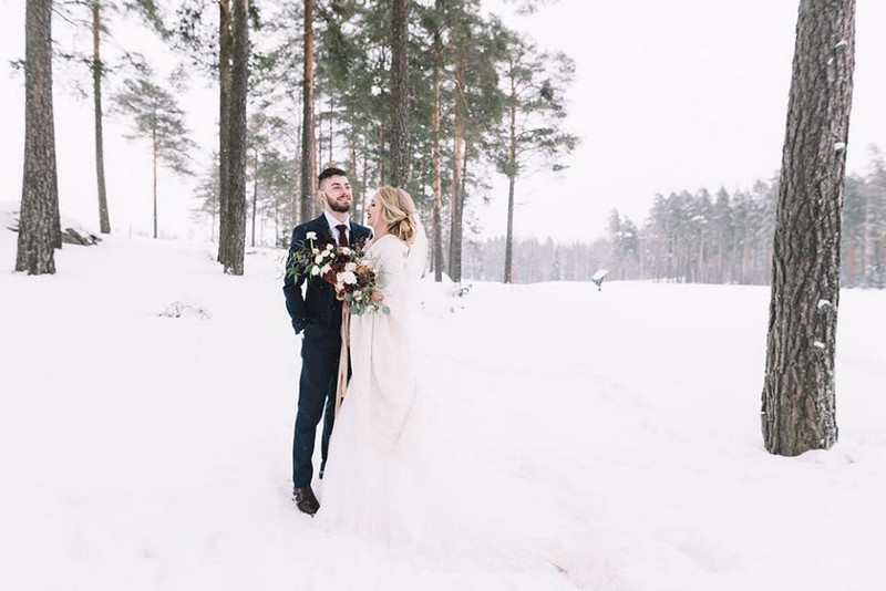Bride and groom standing in the snow - Picture by Lucie Watson Photography