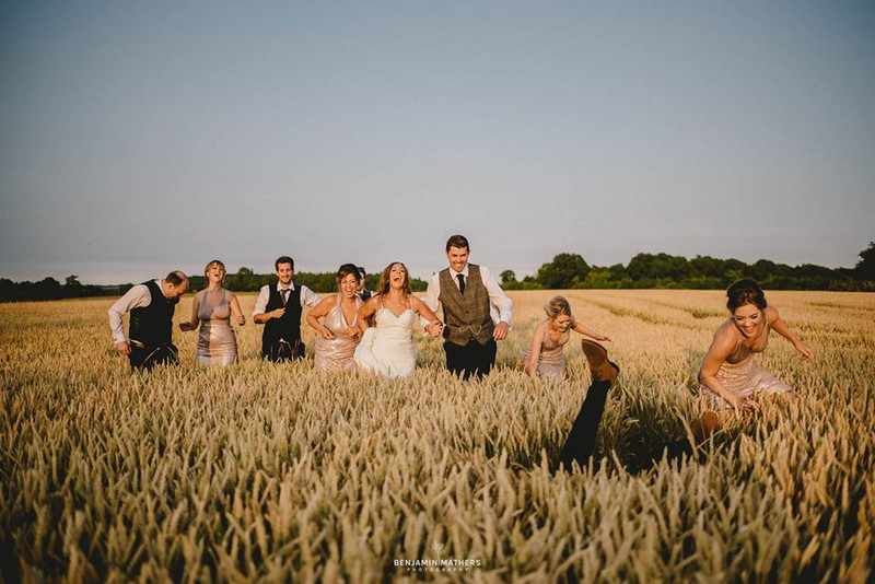 Man falling over as bridal party walk across corn field - Picture by Benjamin Mathers Photography