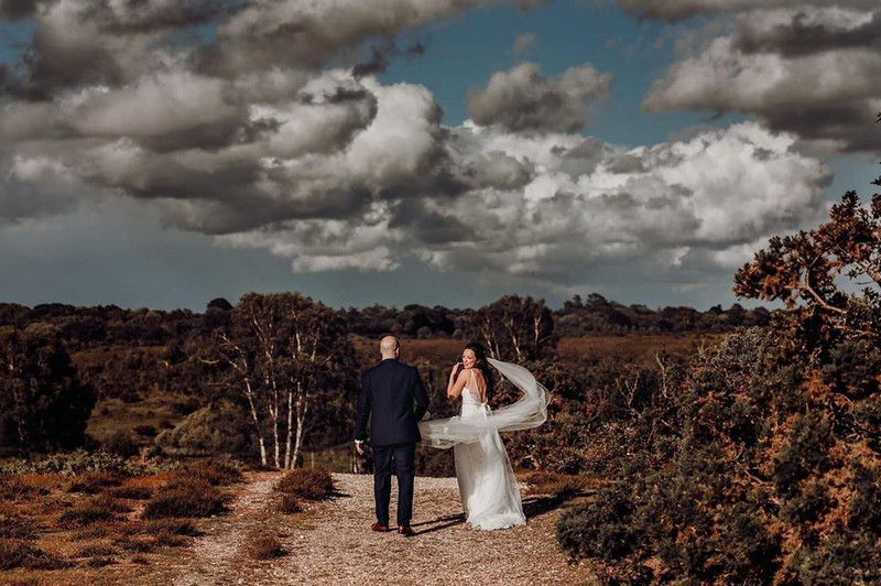 Bride and groom walking on path in countryside - Picture by Romy Lawrence Photography