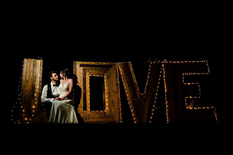 Bride and groom sitting by wooden illuminated LOVE letters - Picture by James Powell Photography