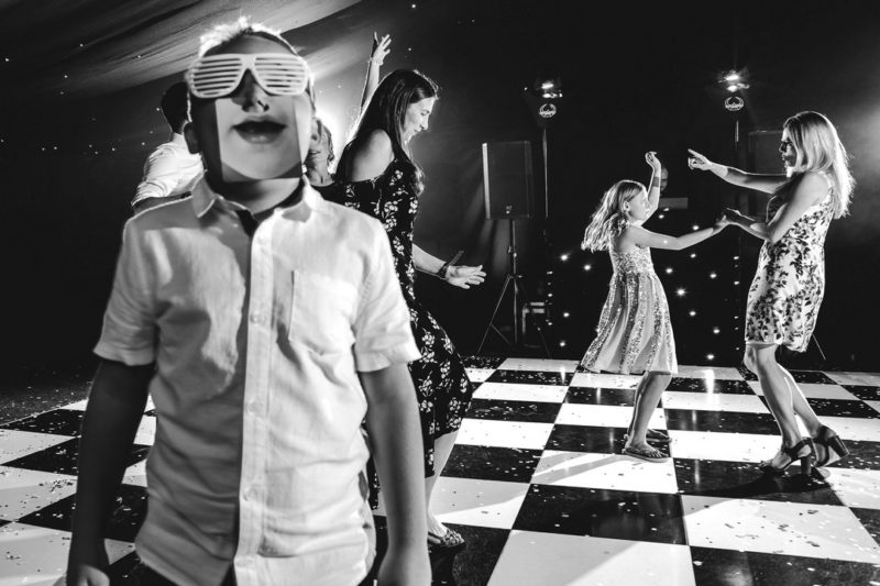 Boy on wedding dance floor wearing lasses and an image of a mouth - Picture by John Woodward Photography