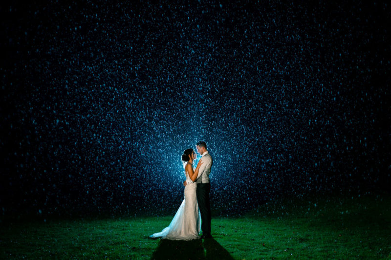 Bride and groom standing in the rain at night - Picture by Dean Jones Photography