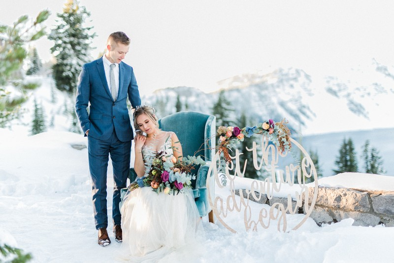 Groom standing next to bride sitting in armchair in snow
