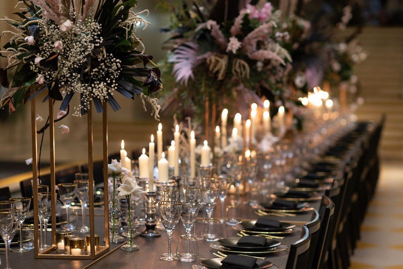 Statement floral displays and candles on long wedding table