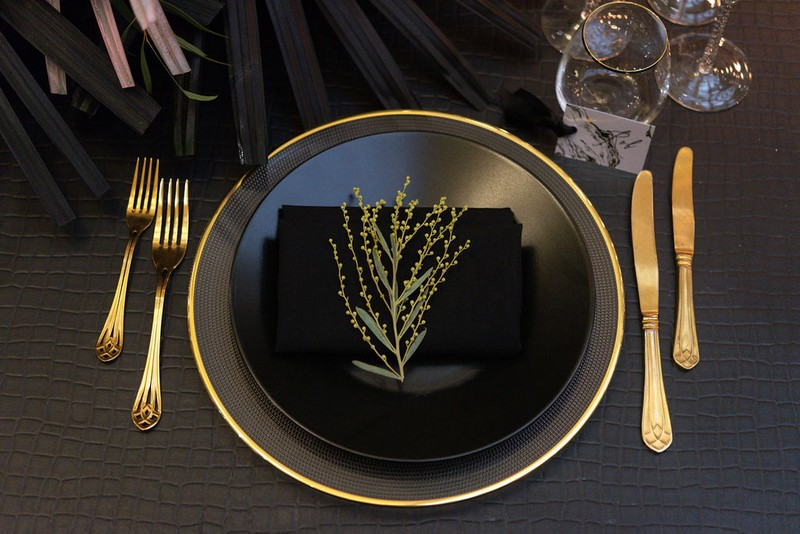Black wedding place setting with gold cutlery