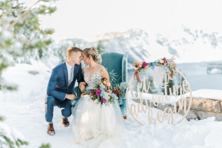 Groom touching heads with bride sitting on chair in the snow