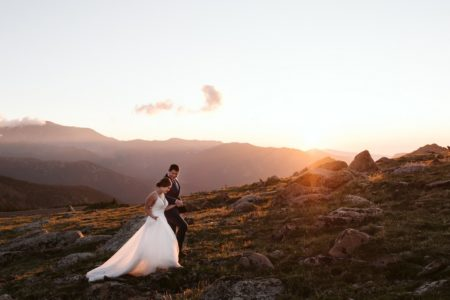 Bride and groom holding hands as they walk up a hill - Picture by Larsen Photo Co.