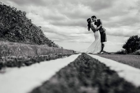 Bride and groom kissing standing in road next to double yellow lines - Picture by Joss Denham Photography
