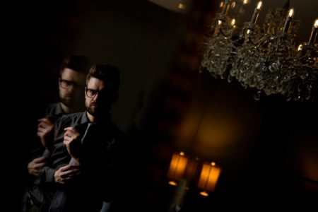 Groom getting ready for wedding in dark room - Picture by Matt Selby Photography