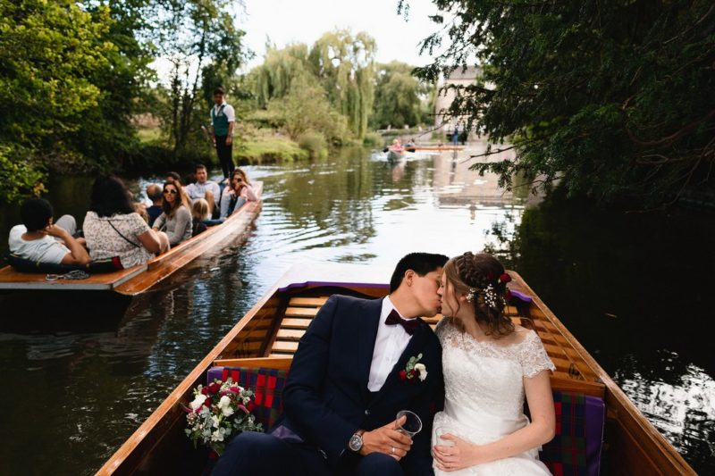 Bride and groom kissing on boat on river - Picture by Sam Gibson Photography