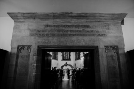 Picture taken through entrance of church of wedding ceremony taking place inside - Picture by BGS Weddings