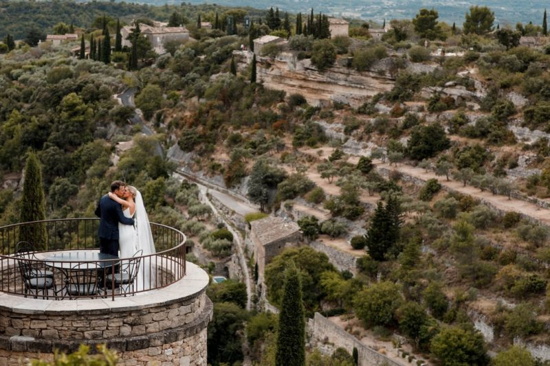 Bride and groom kissing on top of tower overlooking town in hills - Picture by Damion Mower Photography