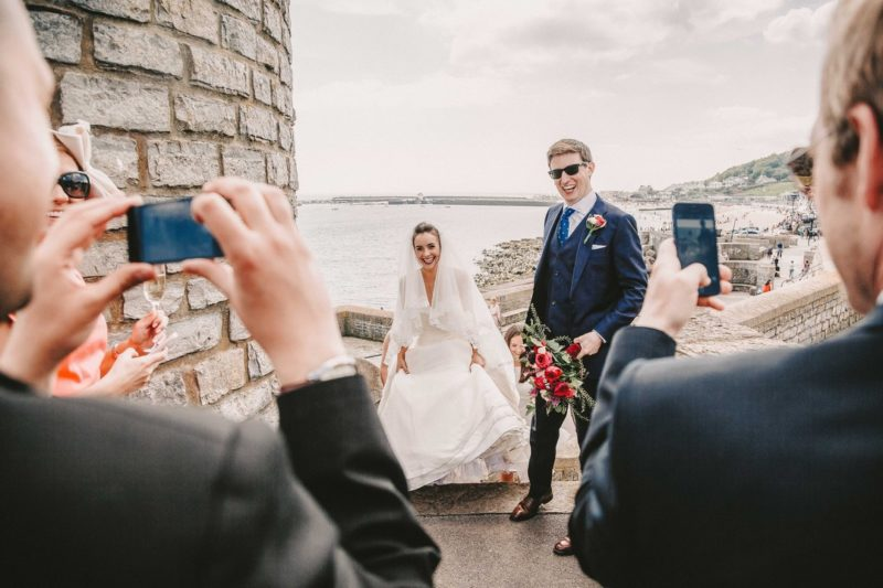 Wedding guests taking photos of bride and groom on their phones