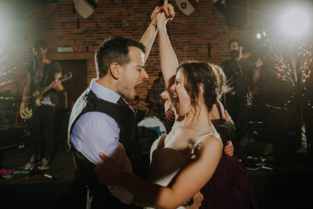Couple enjoying their first dance at their wedding in front of band
