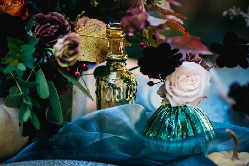 Coloured glass bottles on wedding table
