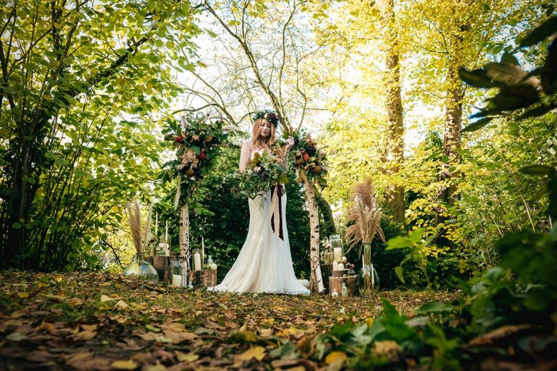 Bride standing in woodland in front of ceremony arch