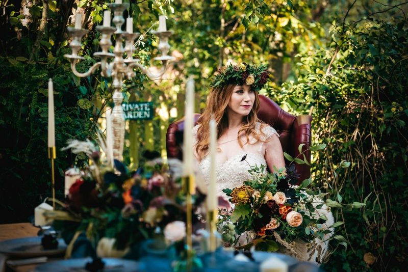 Bride sitting on red leather chair in woodland