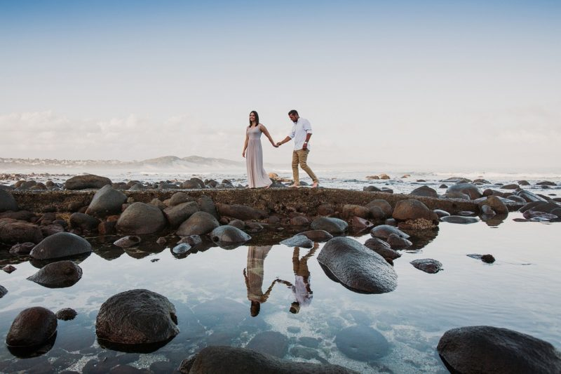 Bride and groom walking holding hands across rockpool - Picture by Estefania Romero Photography