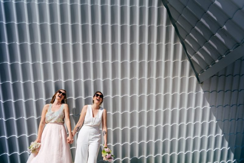 Two brides wearing sunglasses holding hands and laughing - Picture by Jordanna Marston Photography