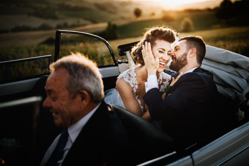Bride and groom laughing in back of convertible wedding car - Picture by Nicola Tonolini