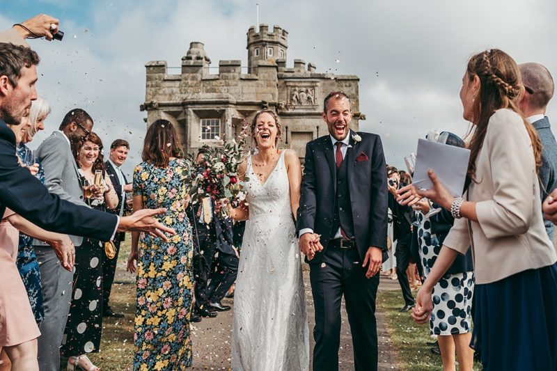 Bride and groom laughing as wedding guests throw confetti over them - Picture by Tracey Warbey Photography