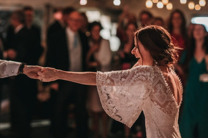 Bride stretching out arm to hold groom's hand during first dance - Picture by Ben Wigglesworth Photography