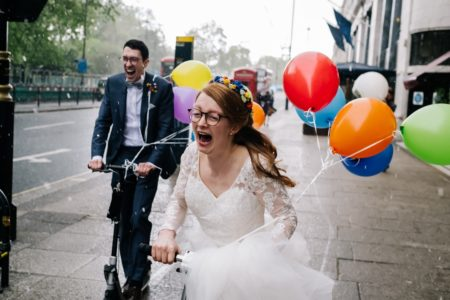 Happy bride and groom riding on scooters pulling balloons - Picture by Kristian Leven Photography