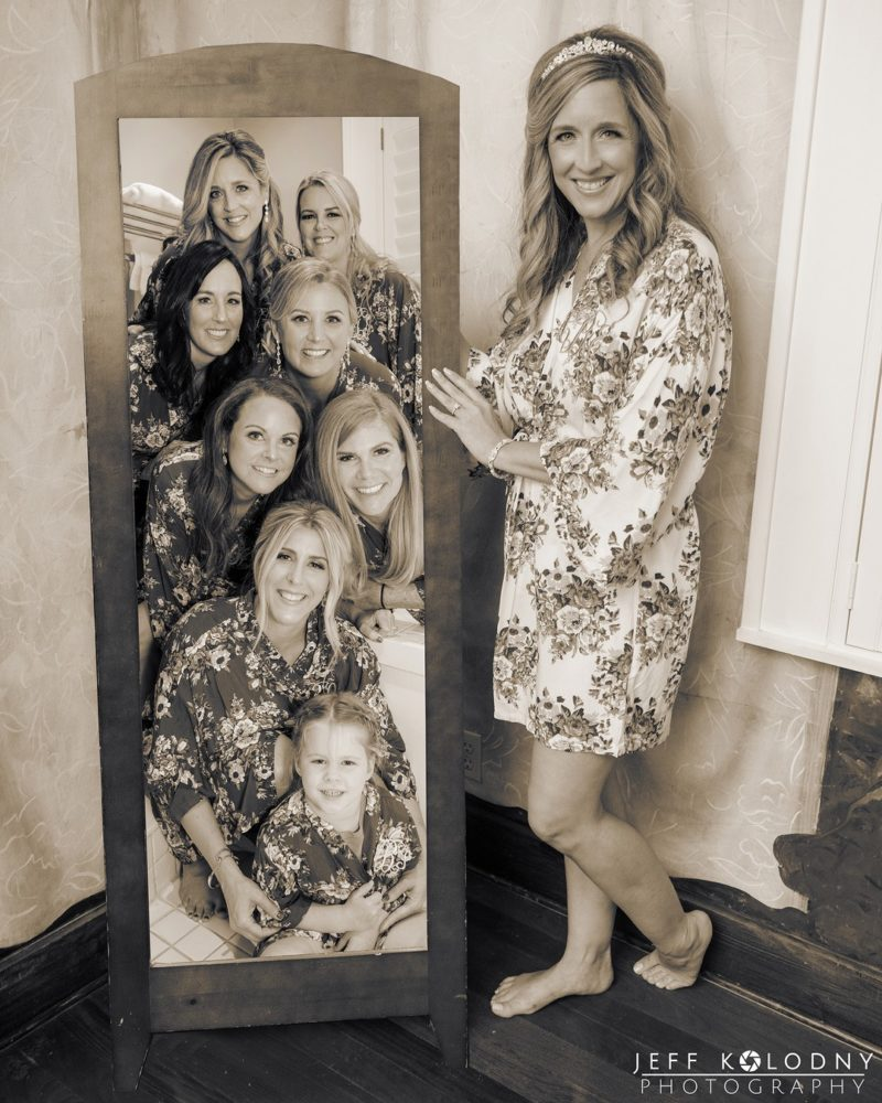 Bride standing next to mirror showing reflection of bridesmaids - Picture by Jeff Kolodny Photography